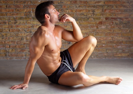 muscle shaped man sitting relaxed on grunge brickwall photo