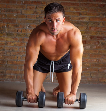 dumb: muscle shaped man on knees with training weights on brickwall Stock Photo