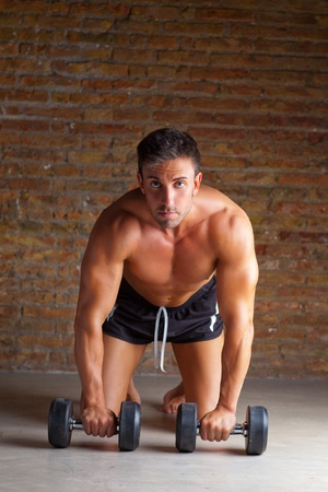muscle shaped man on knees with training weights on brickwall photo