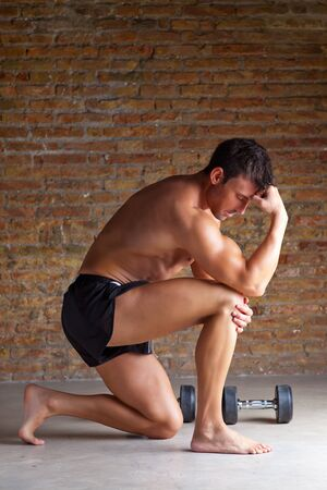 muscle shaped man on knee thinking with thinker posture photo
