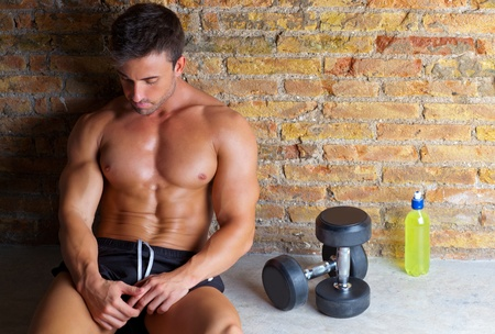 bell shaped: muscle shaped man tired sitting relaxed with weights and energy drink Stock Photo