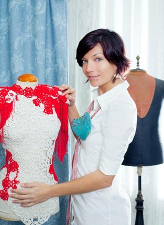 Dressmaker with mannequin as professional fashion designer photo