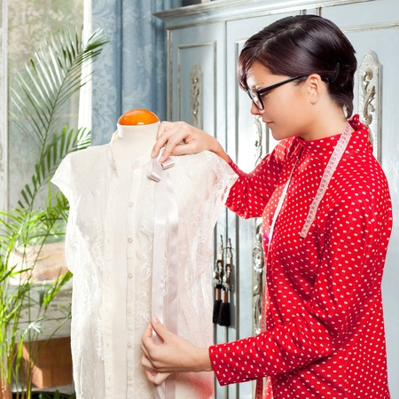 Dressmaker with mannequin as professional fashion designer photo