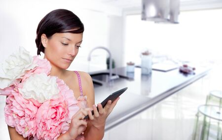 fashion woman and tablet ebook reading on kitchen with spring pink flowers dress photo