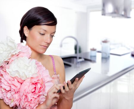 fashion woman and tablet ebook reading on kitchen with spring pink flowers dress Stock Photo - 12144709