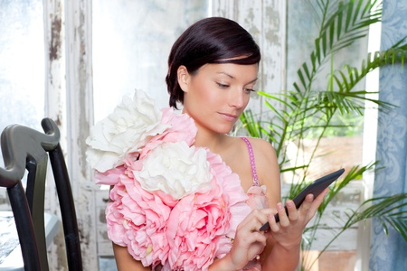 fashion woman and tablet ebook reading at home with spring pink flowers dress photo