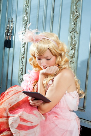 blond fashion princess woman reading ebook tablet with retro spring pink dress photo