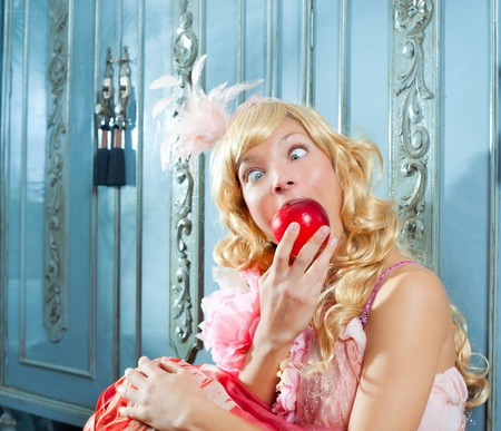 blond fashion princess eating apple with funny eyes expression photo