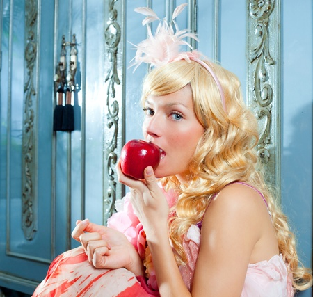 blond fashion princess eating apple with spring flowers dress on blue wardrobe photo