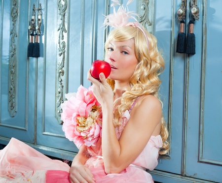 haute: blond fashion princess eating apple with spring flowers dress on blue wardrobe