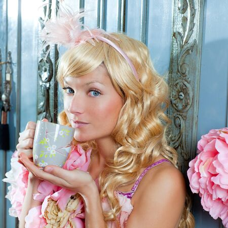 blond fashion princess woman drinking tea or coffee at home with vintage pink dress photo