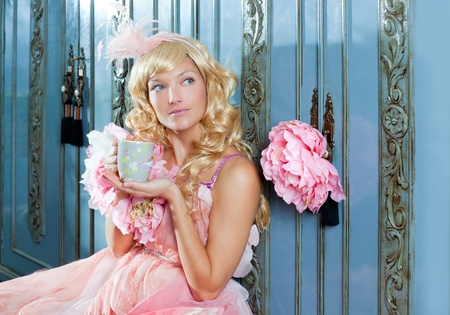 seductive women: blond fashion princess woman drinking tea or coffee at home with vintage pink dress