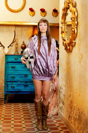 Futuristic fashion woman in retro grunge home with steel helmet photo