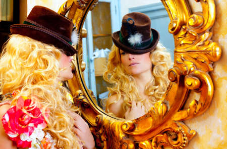fashion blond woman with hat looking in baroque golden frame mirror photo