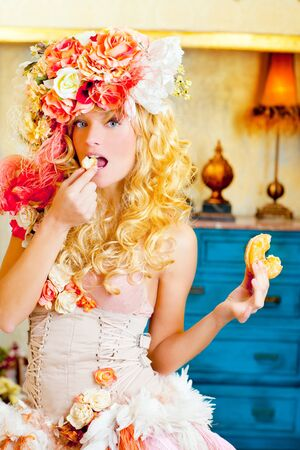 baroque fashion blonde woman eating bagel with flowers hat photo