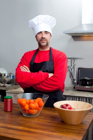 culinary skills: Chef man portrait with mustache in black and red on the kitchen Stock Photo
