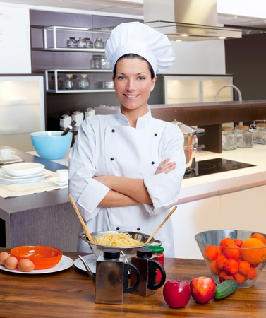 culinary skills: Chef woman portrait with white uniform in the kitchen Stock Photo