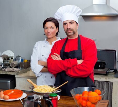 culinary skills: Chef couple man and woman posing in kitchen with uniform