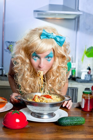 Blonde funny girl on kitchen eating pasta like crazy with blue makeup Stock Photo - 12148129