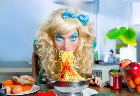crazy girl: Blonde funny girl on kitchen eating pasta like crazy with blue makeup
