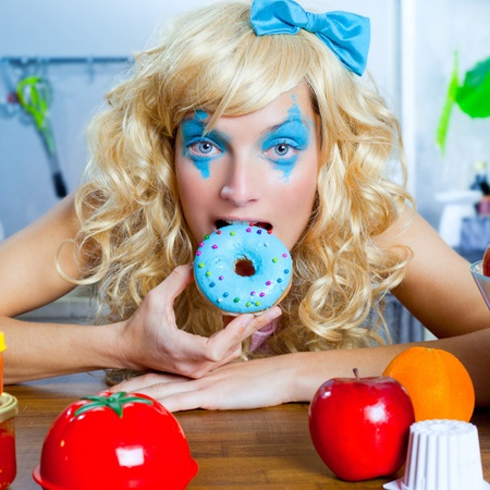 tacky: Blonde funny girl on kitchen eating blue donut with fashion makeup Stock Photo