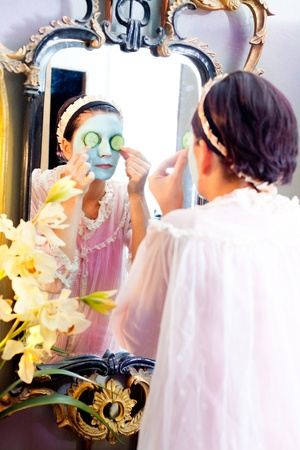 Funny housewife beauty green clay mask and cucumber at the mirror photo