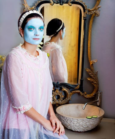 Funny housewife beauty treatment green clay mask at the mirror photo
