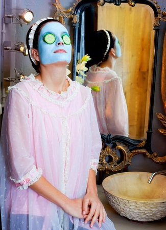 Funny housewife beauty green clay mask and cucumber at the mirror Stock Photo - 12148079