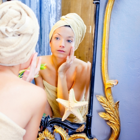 animal masks: Beauty woman with towel looking at golden mirror putting cream Stock Photo