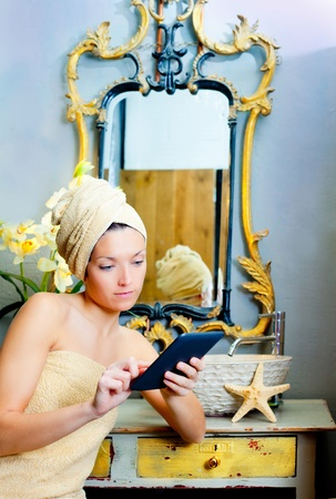 Female in bathroom reading ebook tablet relaxed photo