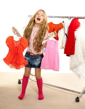 fashion victim kid girl at backstage wardrobe choosing clothes photo