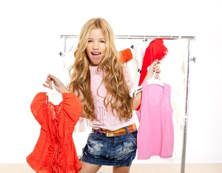 choosing clothes: fashion victim kid girl at backstage wardrobe choosing clothes