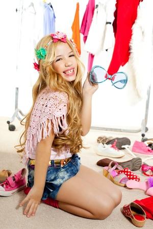 fashion victim kid girl wardrobe messy playing with sunglasses photo