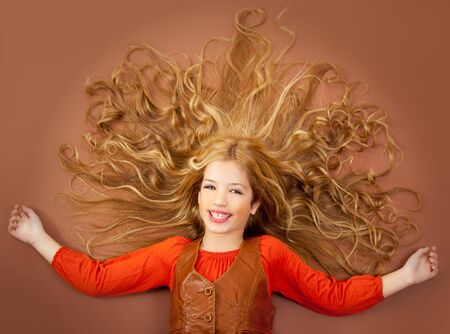 autumn fall little blond girl on brown background and long spreaded hair photo