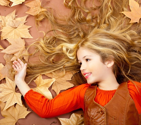 autumn fall little blond girl on dried tree leaves background and long spread hair photo