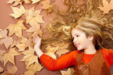 curly hair child: autumn fall little blond girl on dried tree leaves background and long spread hair