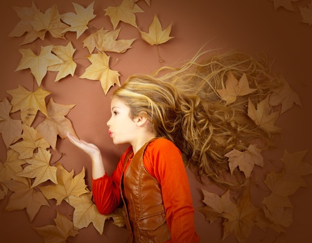 autumn fall little blond girl on dried tree leaves blowing wind with lips photo
