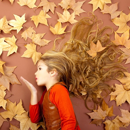 girl blowing: autumn fall little blond girl on dried tree leaves blowing wind with lips