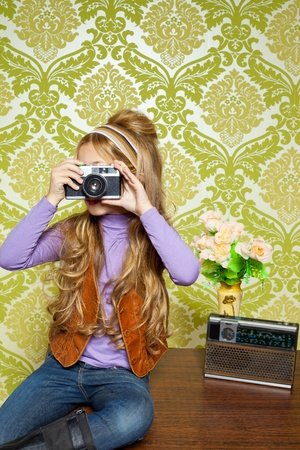 photo shooting: hip retro little girl shooting photo with vintage camera on wallpaper Stock Photo