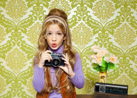 hip retro little girl shooting photo with vintage camera on wallpaper photo