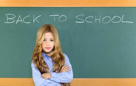 kid student girl on green school blackboard with written back to school text photo