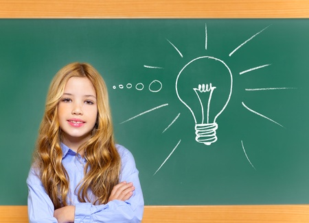 kid student girl on green school blackboard and drawn light bulb idea photo