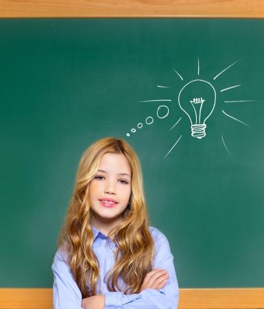 kid student girl on green school blackboard and drawn light bulb idea Stock Photo - 12148228