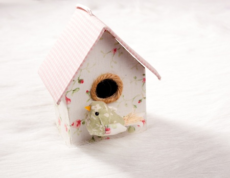 bird in a nest fabric house with round window in pastel colors photo