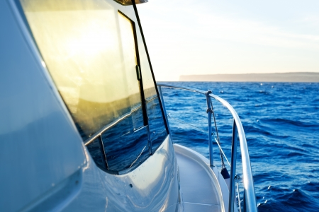 blue golden sunrise sailing on boat side with Mediterranean coastline in horizon photo