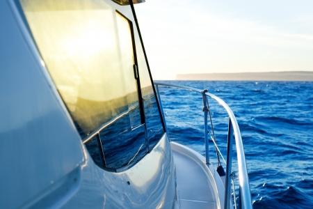 coastline: blue golden sunrise sailing on boat side with Mediterranean coastline in horizon