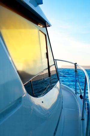 blue golden sunrise sailing on boat side with Mediterranean coastline in horizon photo