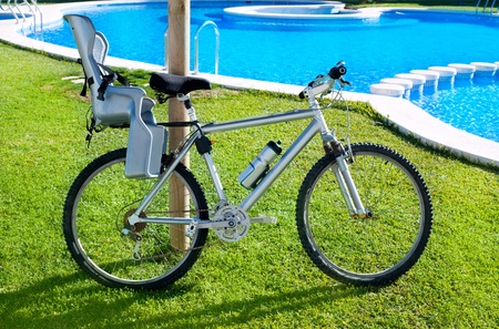 bicycle with baby seat in grass pool outdoor on summer vacation photo