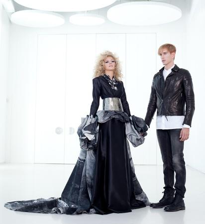 haute: Black haute couture retro futurist couple in modern white hall with vampire inspiration Stock Photo