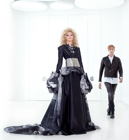 haute couture: Black haute couture retro futurist couple in modern white hall with vampire inspiration Stock Photo